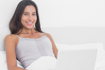 Portrait of a pretty woman using her laptop in bed