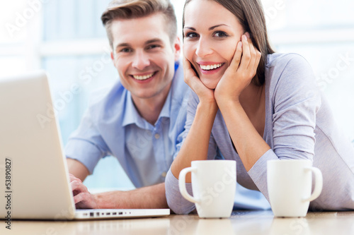 Couple on floor using laptop