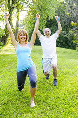 Personal trainer with client exercising outdoors