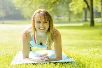 Woman holding plank pose outside