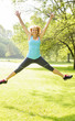 Smiling woman jumping in park