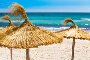Beach, blue sea and straw umbrellas on Mallorca island, Spain