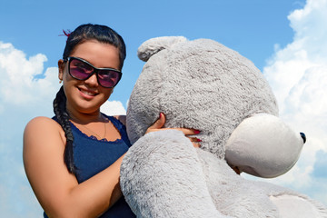 A girl with a gray teddy bear