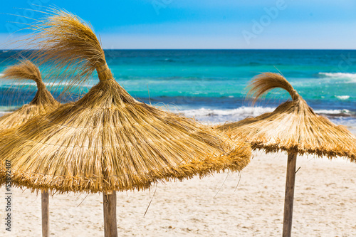 Beach, blue sea and straw umbrellas on Mallorca island, Spain