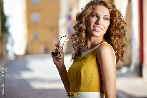 young woman in summer dress against old city wall, outdoor shot
