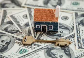 Many dollar banknotes, key and a house model