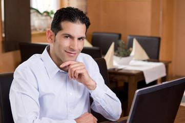Entspannt lächelnder Geschäftsmann im Bistro