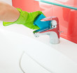 Woman cleaning sink and faucet