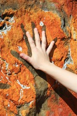 hand and painting on rock