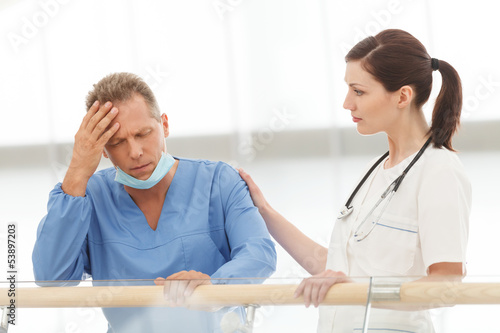 Depressed surgeon. Young female doctor comforting her depressed