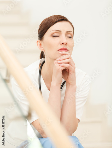 Tired and depressed. Beautiful young female doctor sitting at th