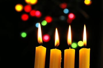 Close up of four candles on black background with copy space.