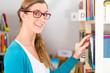 Mädchen in Bibliothek nimmt Buch aus Regal