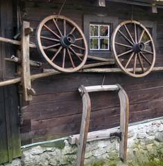 Wagon wheel on old log house