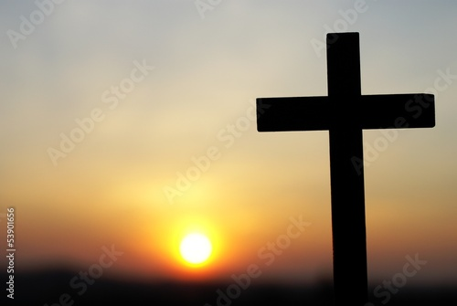 Silhouette of wooden cross on sky background