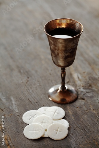 Chalice with wine and communion wafers on wooden background