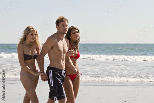 Friends Walking Along Beach