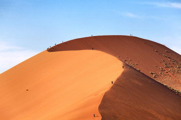 dunes in the desert with people walking on the sand
