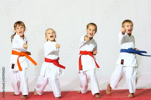 canvas print picture Four children in kimono hit a punch on a white background