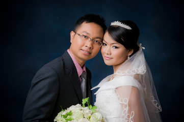 Bride and Groom posing in wedding dress at studio, smiling