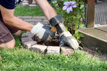 Pflastersteine werden im Garten um Beet gestetzt