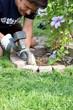 Mann verlegt Pflastersteine um Blumenbeet
