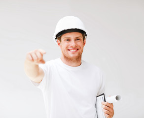 male architect in helmet pointing at you