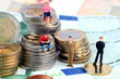 Männchen sitzen auf Euomünzen, Finanzen, Geld