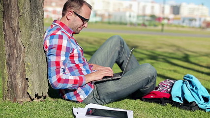 Young student with laptop sitting in the park