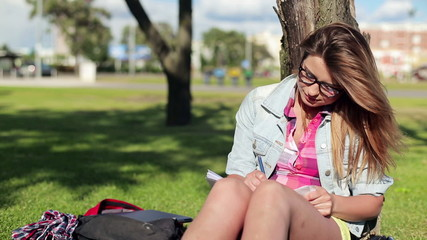 Pretty female student studying in the park