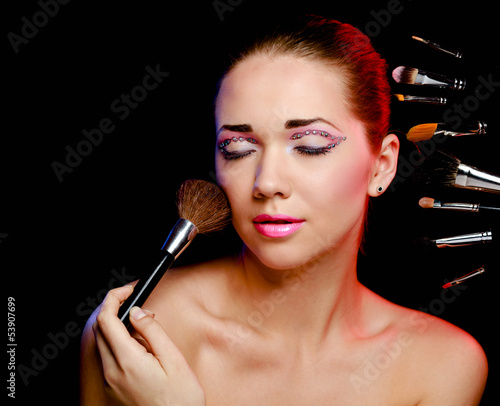 Beautiful young adult woman holds the make-up brushes