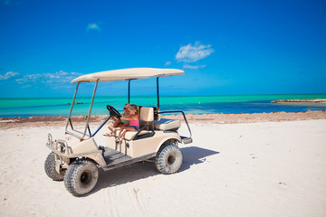 two daughters and their mother driving golf cart at tropical