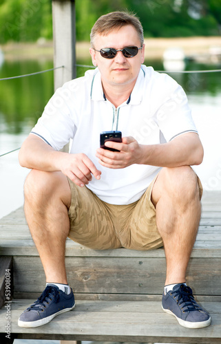 Mature man with sunglasses sitting at pier