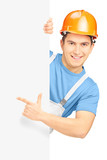 Young smiling construction worker with helmet pointing on a pane