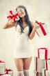 Beautiful woman as angel with heap of gift boxes posing indoors