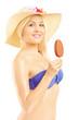 Beautiful blond woman in bikini eating an ice cream