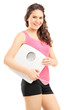 Smiling female athlete holding a weight scale and looking at cam