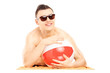 Smiling guy lying on a beach towel and holding a ball
