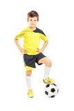 Full length portrait of a kid in sportswear posing with a soccer