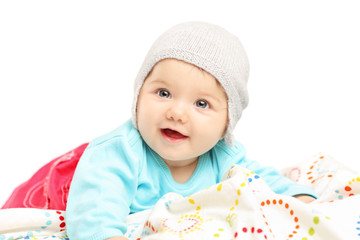 Baby girl with hat lying down and smiling