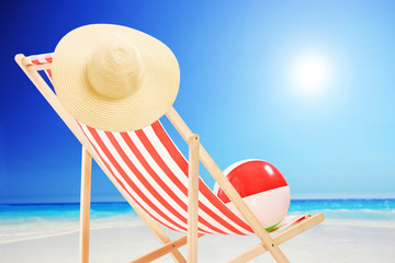 Beach chair with ball and hat by the sea