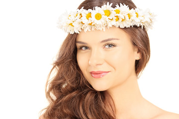 Beautiful young female with a daisy hair wreath looking at camer