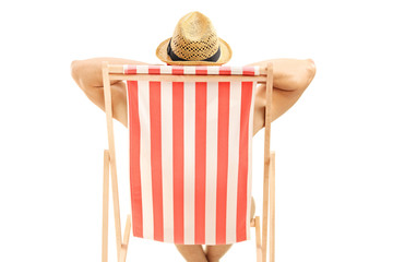 Man with hat sitting on a beach chair