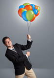 Handsome man holding colorful balloons
