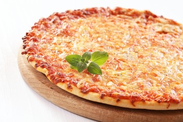 Pizza with cheese and fresh oregano on a wooden tray.