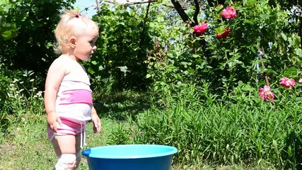 little girl playing in basin with water, summer day