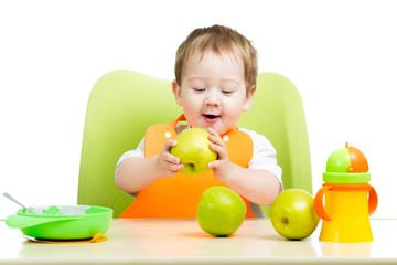 cute baby boy eating apple