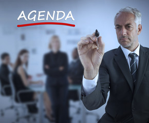 Sophisticated businessman underlining in red the word agenda