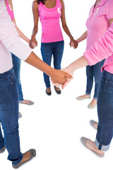 Women wearing pink and ribbons for breast cancer holding hands i
