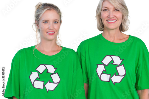 Two women wearing green recycling tshirts
